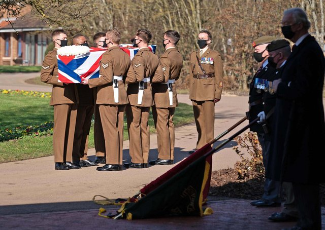 BEDFORD, ENGLAND - FEBRUARY 27: (No reuse after 11.59pm on March 6th 2021 without written consent from gemma@captaintom.org.) The coffin of Captain Sir Tom Moore is carried by members of the Armed Forces during his funeral at Bedford Crematorium on February 27, 2021 in Bedford, England. WWII veteran, Sir Tom raised nearly £33 million for NHS charities ahead of his 100th birthday last year by walking laps of his garden in Marston Moretaine, Bedfordshire. He died on the 2nd of February after testing positive for COVID-19. (Photo by Joe Giddens - Pool/Getty Images)