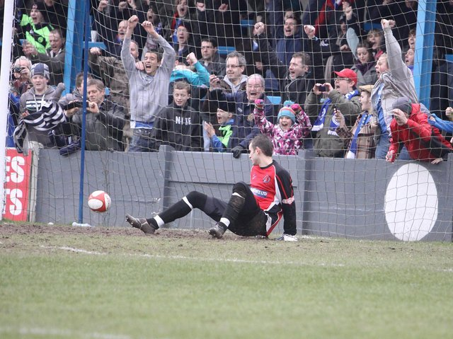 Halifax Town fans cheer as Buxton keeper Scott Hartley is sent the wrong way from the penalty spot.