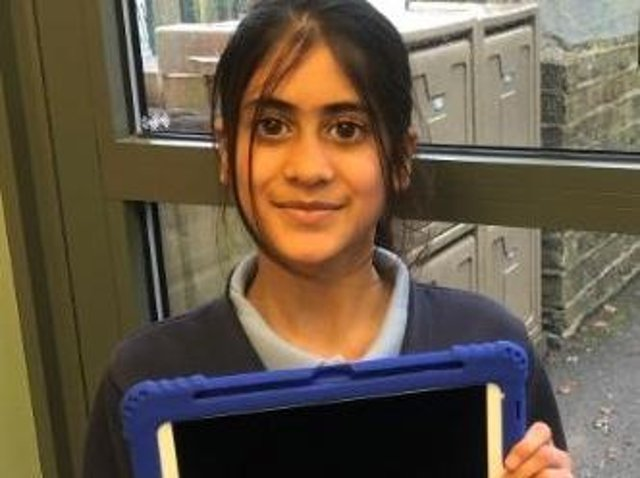 School student holding one of the newly gifted ipads funded by Rotary.