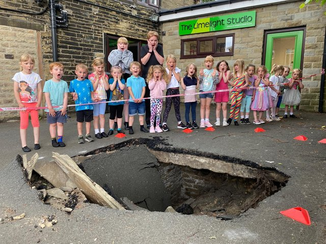 Members of Limelight Theatre school with a huge sink hole outside their building